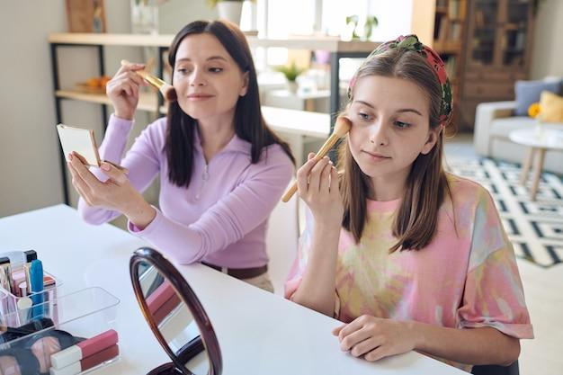 Hübsche mutter und tochter im teenageralter sitzen am tisch im wohnzimmer und verwenden pinsel beim schminken