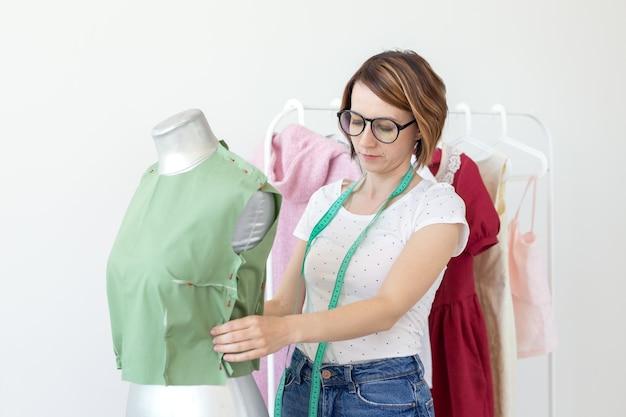 Hübsche näherin frau in gläsern mit einem maßband macht eine grüne bluse mit der hilfe