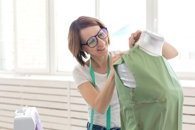 Hübsche näherin frau in gläsern mit einem maßband macht eine grüne bluse mit hilfe einer schneiderpuppe und sicherheitsnadeln. konzept einer eigenen nähwerkstatt.