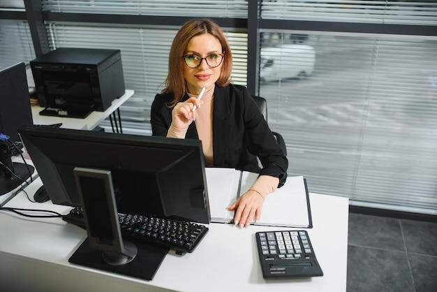 Hübsche, nette, süße, perfekte frau, die an ihrem schreibtisch auf ledersessel am arbeitsplatz sitzt, brille, abendgarderobe trägt, laptop und notizbuch auf dem tisch hat