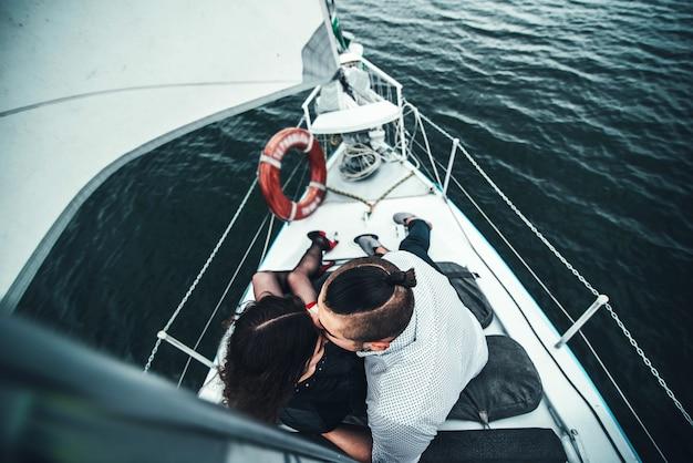 Hübsche paare im freien, die auf der yacht sich entspannen