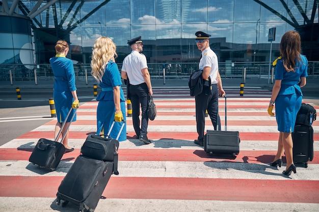 Hübsche piloten und charmante flugbegleiter, die trolley-gepäcktaschen beim gehen auf einem fußgängerüberweg tragen
