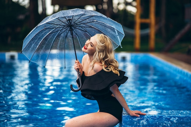 Hübsche pin-up-blondine im schwarzen vintage-badeanzug, die sich im pool entspannt
