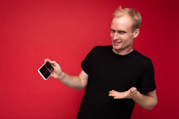 Hübsche positive glückliche blonde junge männliche person, die ein schwarzes t-shirt trägt, das isoliert auf rot steht