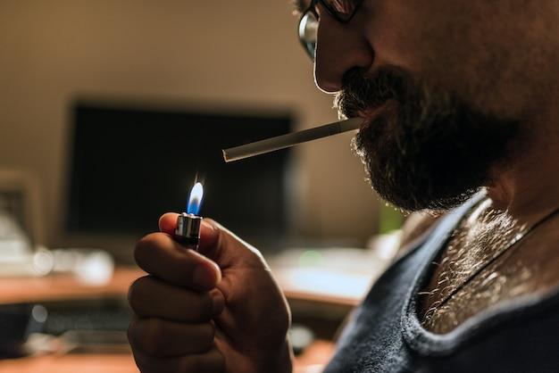 Hübsche rauchende zigarette des jungen mannes