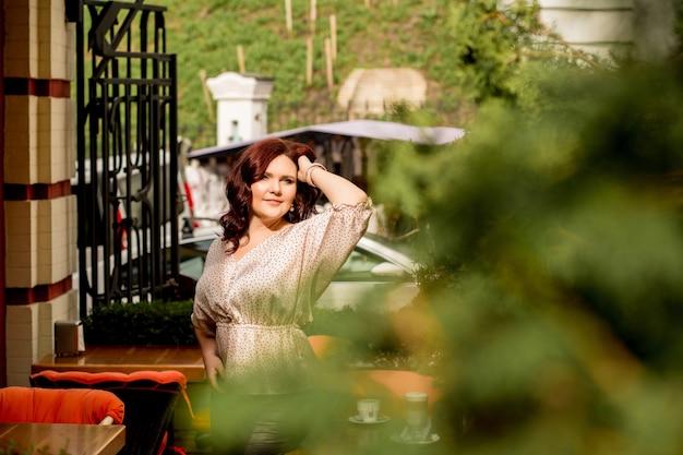 Hübsche reife rothaarige dame in seidenbluse posiert auf einer terrasse mit thuja-baum. platz für text