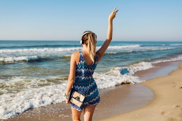 Hübsche reisende frau, die musik am strand hört