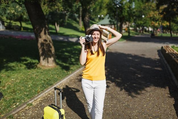 Hübsche reisende touristenfrau mit hut mit kofferstadtplan fotografieren auf retro-vintage-fotokamera in der stadt im freien. mädchen, das ins ausland reist, um am wochenende zu reisen. tourismus reise lebensstil.