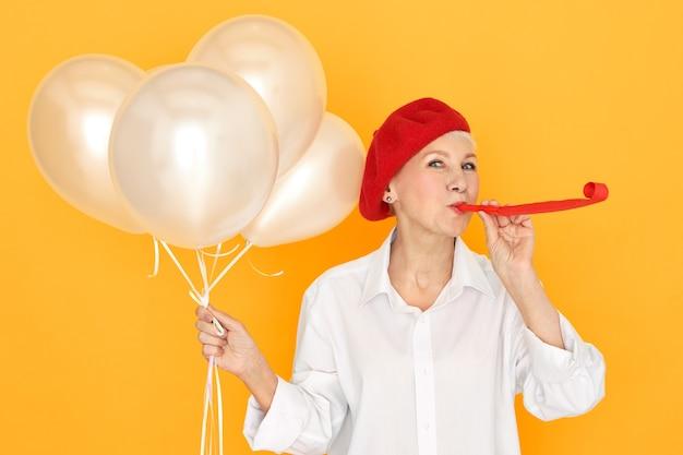 Hübsche rentnerin in der roten haube genießt party, unterhält ihre enkelkinder, die pfeife blasen und weiße heliumballons halten