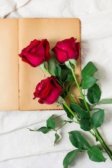 Hübsche rote rosen der draufsicht auf einem buch