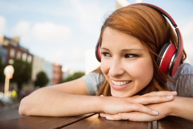 Hübsche rothaarige, die auf der bank hört musik liegt