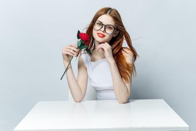 Hübsche rothaarige frau, die am tisch mit rosenblume in ihren händen glamouröse rote lippen modell sitzt