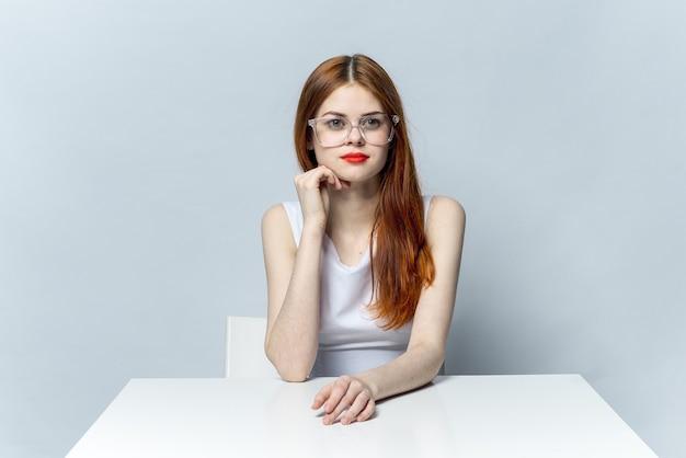 Hübsche rothaarige frau, die am tisch sitzt und die roten lippen der brille trägt, lächelt leicht