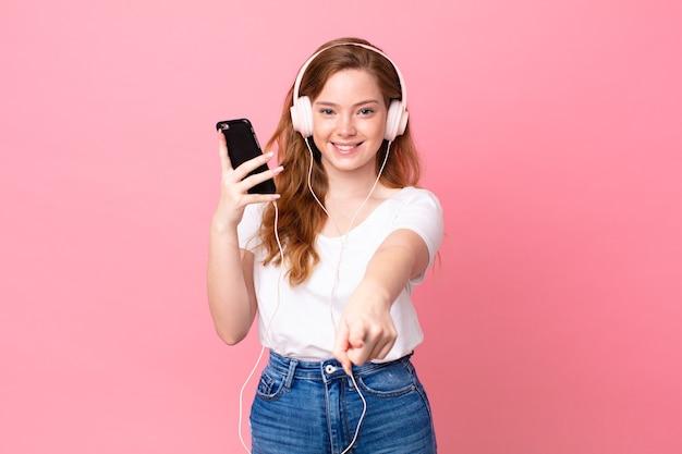 Hübsche rothaarige frau, die auf die kamera zeigt und dich mit kopfhörern und smartphone auswählt