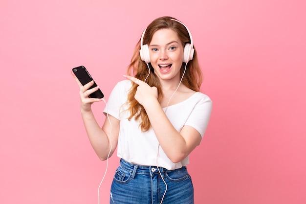 Hübsche rothaarige frau, die aufgeregt und überrascht aussieht und mit kopfhörern und smartphone auf die seite zeigt