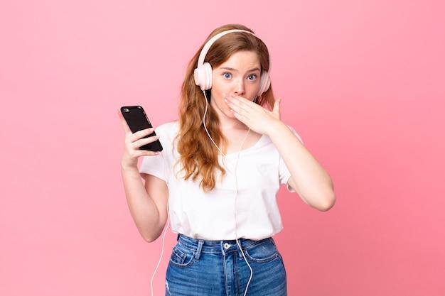 Hübsche rothaarige frau, die den mund mit den händen bedeckt, mit einem schockierten mit kopfhörern und smartphone