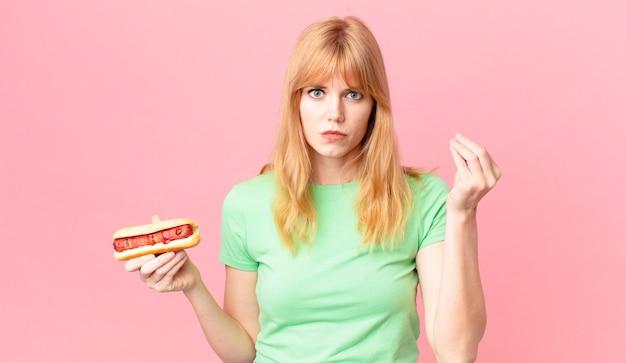 Hübsche rothaarige frau, die eine capice- oder geldgeste macht, ihnen sagt, dass sie bezahlen und einen hot dog halten sollen?