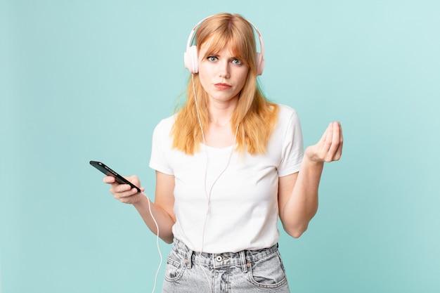 Hübsche rothaarige frau, die eine capice- oder geldgeste macht und ihnen sagt, dass sie bezahlen und musik mit kopfhörern hören sollen
