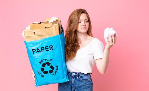 Hübsche rothaarige frau, die eine recyclingpapiertüte hält