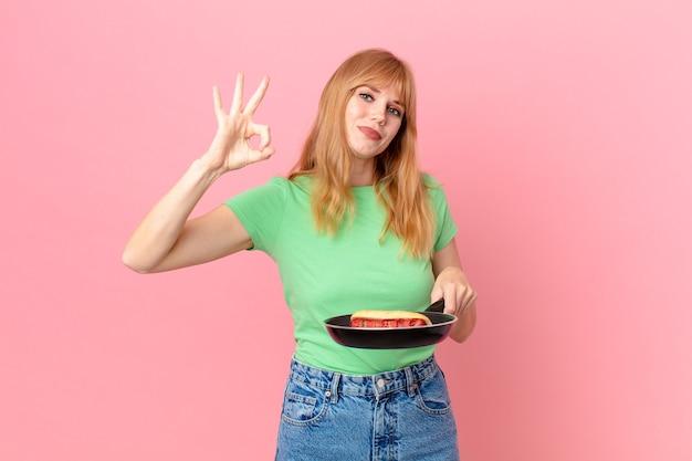 Hübsche rothaarige frau, die einen hotdog mit einer pfanne kocht