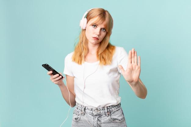 Hübsche rothaarige frau, die ernst aussieht und offene handfläche zeigt, die stopp-geste macht und musik mit kopfhörern hört