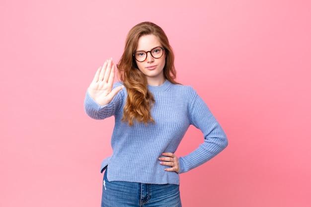 Hübsche rothaarige frau, die ernst aussieht und offene handfläche zeigt, die stopp-geste macht