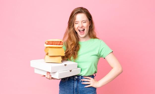 Hübsche rothaarige frau, die fast-food-boxen zum mitnehmen hält