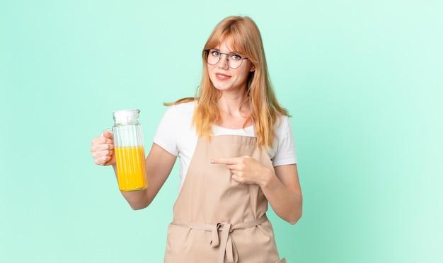 Hübsche rothaarige frau, die fröhlich lächelt, sich glücklich fühlt und mit schürze auf die seite zeigt, die einen orangensaft zubereitet