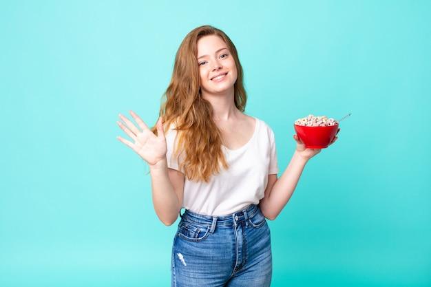 Hübsche rothaarige frau, die glücklich lächelt, die hand winkt, sie begrüßt und begrüßt und eine frühstücksschüssel hält?