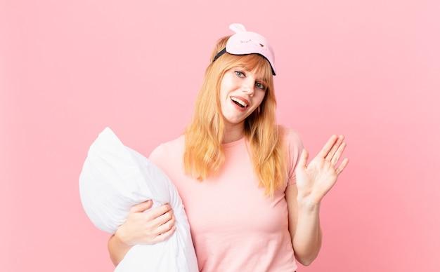 Hübsche rothaarige frau, die glücklich lächelt, hand winkt, sie begrüßt und begrüßt. pyjama tragen und ein kissen halten