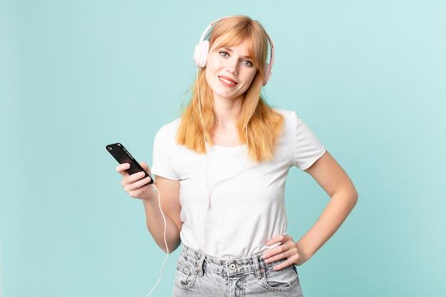 Hübsche rothaarige frau, die glücklich mit einer hand auf der hüfte lächelt und selbstbewusst und musik mit kopfhörern hört