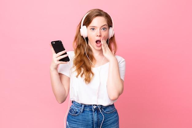 Hübsche rothaarige frau, die mit kopfhörern und smartphone schockiert und verängstigt ist