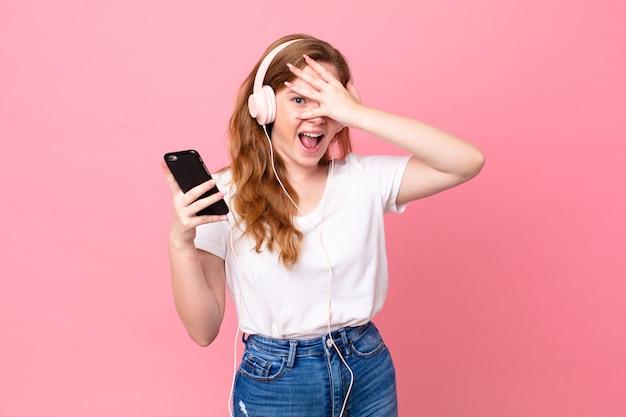 Hübsche rothaarige frau, die schockiert, verängstigt oder verängstigt aussieht und das gesicht mit der hand mit kopfhörern und smartphone bedeckt