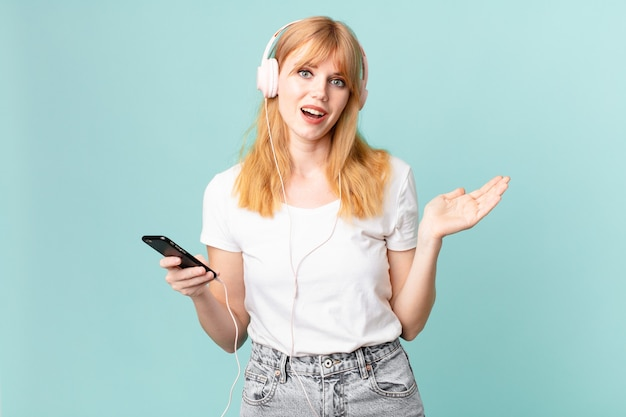 Hübsche rothaarige frau, die sich glücklich fühlt, überrascht, eine lösung oder idee zu realisieren und musik mit kopfhörern zu hören