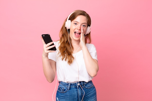 Hübsche rothaarige frau, die sich glücklich fühlt und mit den händen neben dem mund mit kopfhörern und smartphone einen großen schrei ausspricht