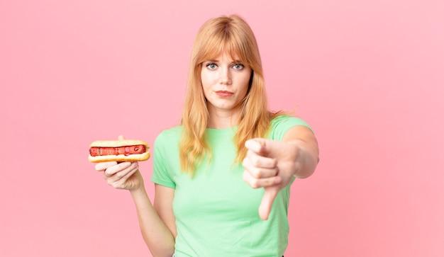 Hübsche rothaarige frau, die sich kreuzen lässt, daumen nach unten zeigt und einen hot dog hält