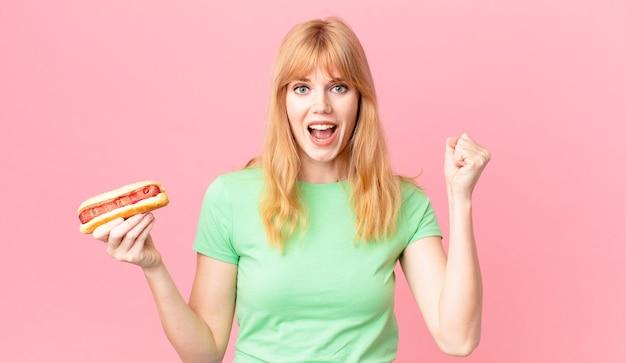 Hübsche rothaarige frau, die sich schockiert fühlt, lacht und den erfolg feiert und einen hot dog hält
