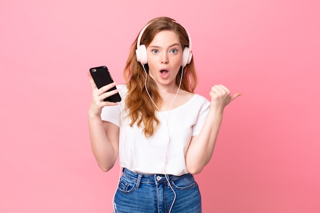 Hübsche rothaarige frau, die ungläubig mit kopfhörern und smartphone aussieht