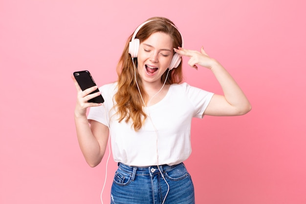 Hübsche rothaarige frau, die unglücklich und gestresst aussieht, selbstmordgeste, die waffenzeichen mit kopfhörern und smartphone macht