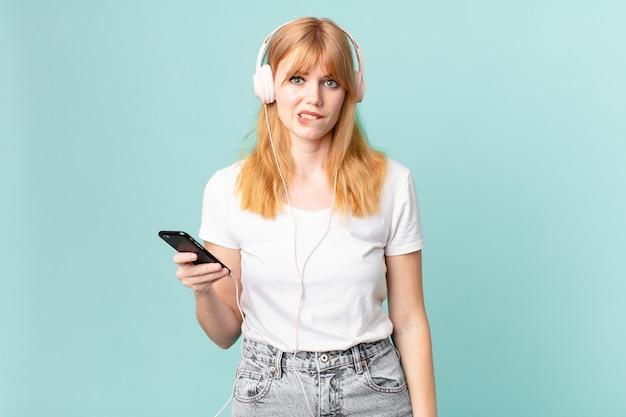 Hübsche rothaarige frau, die verwirrt und verwirrt aussieht und musik mit kopfhörern hört