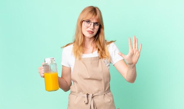 Hübsche rothaarige frau lächelt und sieht freundlich aus und zeigt nummer fünf mit schürze, die einen orangensaft zubereitet