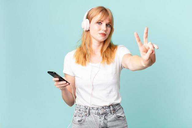 Hübsche rothaarige frau lächelt und sieht freundlich aus, zeigt nummer zwei und hört musik mit kopfhörern