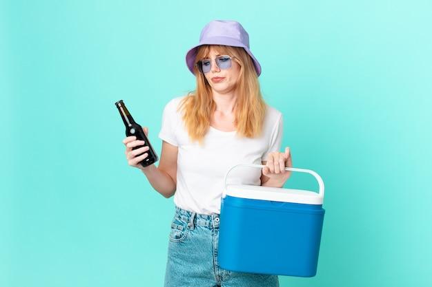 Hübsche rothaarige frau mit einem tragbaren kühlschrank und einem bier