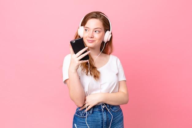 Hübsche rothaarige frau zuckt mit den schultern, fühlt sich verwirrt und unsicher mit kopfhörern und smartphone