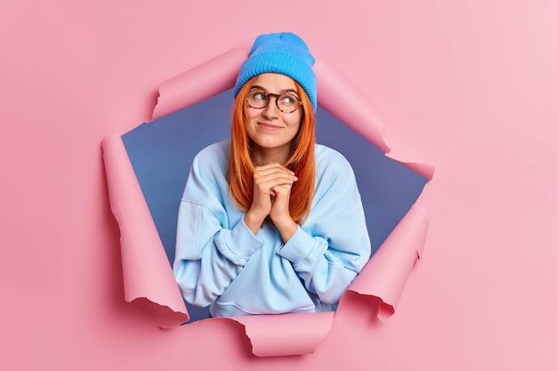 Hübsche rothaarige junge europäische frau hält hände zusammen sieht hoffentlich über lächeln sanft trägt blauen hut sweatshirt.