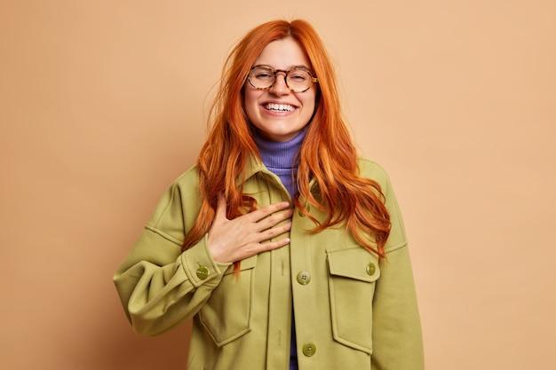Hübsche rothaarige junge frau hält hand auf brust und lächelt breit hat weiße zähne drückt aufrichtige gefühle aus fühlt sich sehr erfreut gekleidet in grüne jacke.