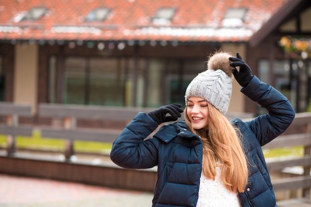 Hübsche rothaarige junge frau mit schwarzem wintermantel und strickmütze, die auf der straße in kiew posiert