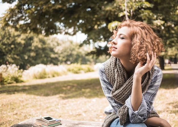 Hübsche rothaarigefrau, die auf bank im park sitzt