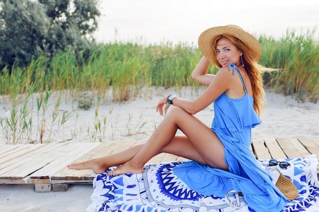 Hübsche schlanke frau mit langen roten haaren im strohhut, die erstaunliche urlaubszeit am strand verbringen. blaues kleid tragen. sitzen auf stilvollem cover.