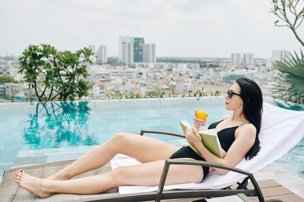 Hübsche schlanke junge frau, die auf chaiselongue nahe infinity-pool mit buch und glas orangensaft und blick auf großstadt entspannt